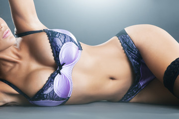 Body of woman with long hair in purple lingerie