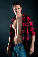 Confident young man with plaid shirt against dark background.