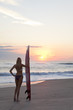 Woman Surfer In Bikini With Surfboard At Sunset Beach