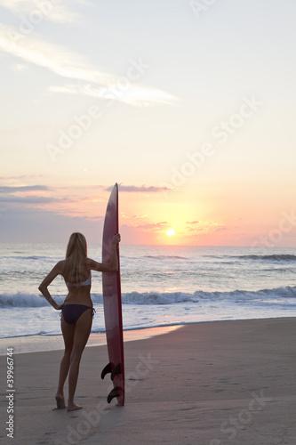 Woman Surfer In Bikini With Surfboard At Sunset Beach