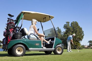 Happy Senior Couple Playing Golf With Cart