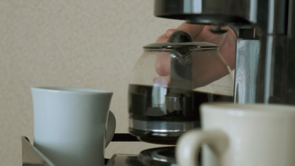 Pouring freshly brewed coffee from carafe