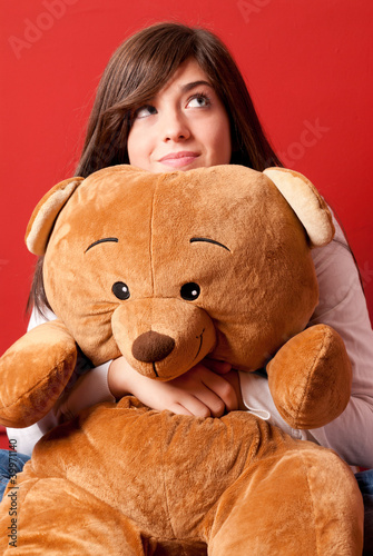Young woman embracing teddy bear looking up sitting close-up