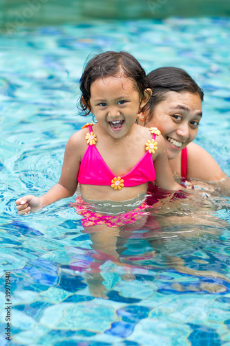 asian child and mother fun in swimming pool