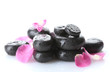 Spa stones with drops and rose petals isolated on white