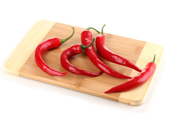 Red hot chili peppers on wooden plank isolated on white