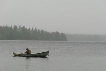 fisherman boat fog rain