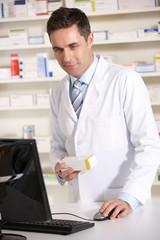 American pharmacist working on computer