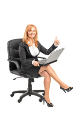 Businesswoman working on a laptop and giving thumb up