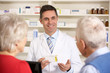 American pharmacist with senior couple in pharmacy