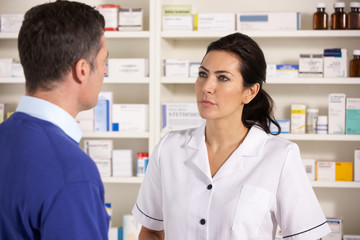 American pharmacist talking to man in pharmacy
