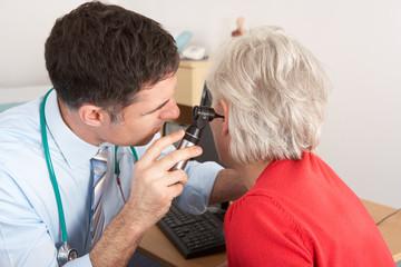 British doctor examining senior woman's ear