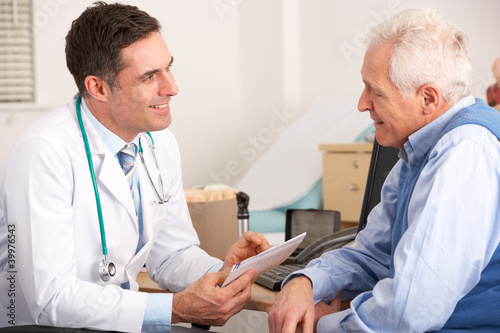 American doctor talking to senior man in surgery - 39976543