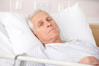 Senior man ill in hospital bed