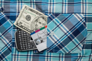 Money, phone and credit card in pocket shirt