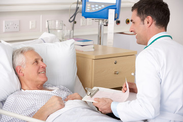 Doctor with senior male patient on USA Hospital ward