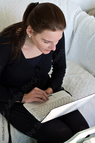 Woman Looking At White Netbook While Sitting On A Couch