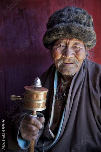 Leinwanddruck Bild Budhist Monk swinging prayer wheel