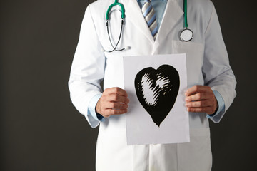 American doctor holding ink drawing of heart