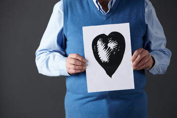 Senior man holding ink drawing of heart