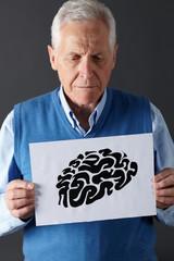 Senior man holding ink drawing of brain