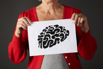 Senior woman holding ink drawing of brain
