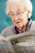 Senior Woman Relaxing In Chair Reading Newspaper