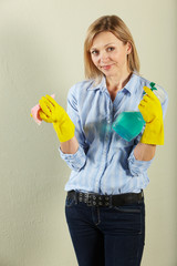 Studio Shot Of Middle Aged Woman Holding Cleaning Products