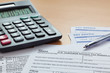 1040 tax return with payslips and calculator