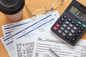 1040 tax form with payslips and calculator