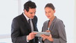 Business man and woman looking at a tablet