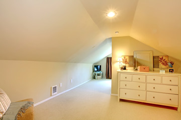 Long attic room with beige colors.