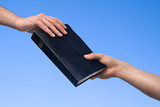 Hand Giving Bible