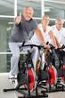 Senior auf Spinning-Rad zeigt Daumen hoch
