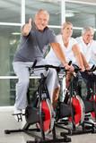 Senior auf Spinning-Rad zeigt Daumen hoch - 39992183
