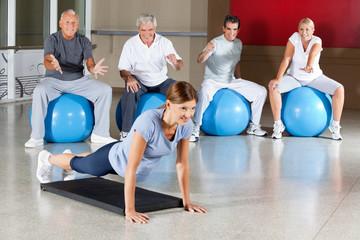 Senioren im Fitnesscenter jubeln Frau zu