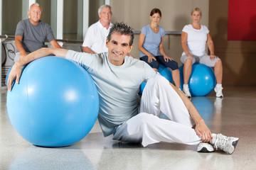 Mann mit Gymnastikball im Fitnesscenter
