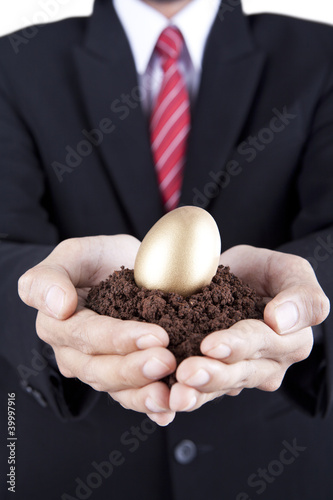Businessman showing golden egg and soil
