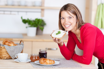lachende frau genießt ihr frühstück zu hause