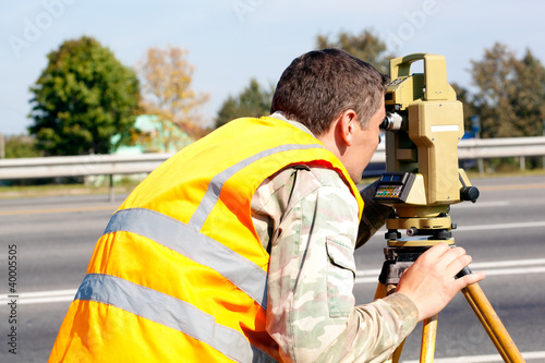 Surveyor engineer making measuring at highway by theodolite
