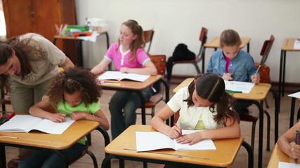 Smiling teacher helping a brunette pupil