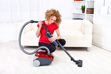 Woman repairs vacuum cleaner