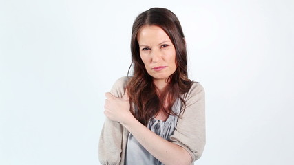 Brunette woman showing her painful shoulder