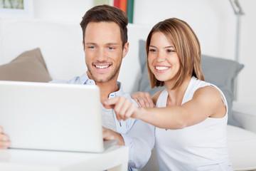 glückliches paar zeigt auf etwas am laptop