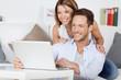 glückliches paar mit laptop auf dem sofa