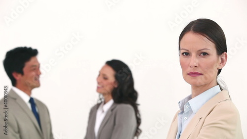 Businesswoman posing with her colleagues talking behind her