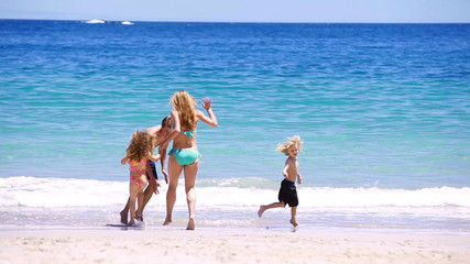 Smiling family running and splashing each other