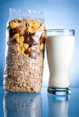 Fresh Glass of Milk and Closed Pack of muesli on a blue backgrou