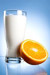 Fresh Glass of Milk and Half of juicy orange on a blue backgroun