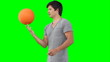A man practises spinning a basketball on his finger